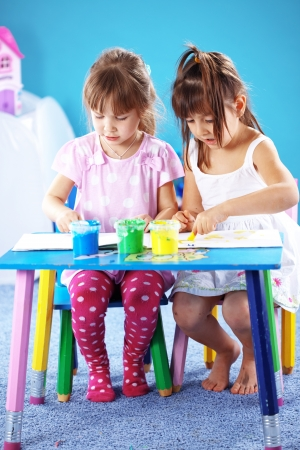 children playing together: Children drawing in the nursery