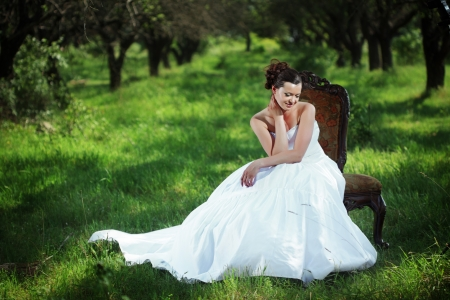 outdoor glamour: Portrait of beautiful bride sitting on the retro char outdoors Stock Photo