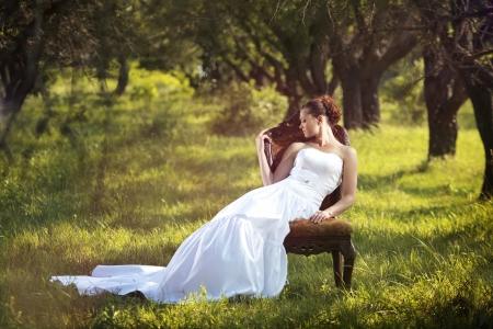 bridal dress: Ritratto di bella sposa seduta sul retro all'aperto char Archivio Fotografico