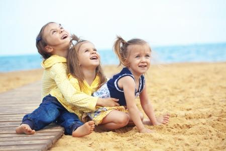 trois enfants: Groupe d'enfants jouant � la plage Banque d'images
