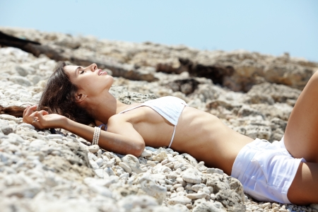 Portrait of beautiful young woman with golden tan resting at beach in summer photo