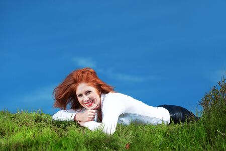 Outdoor portrait of beautiful readheaded girl resting on grass over blue sky at spring photo