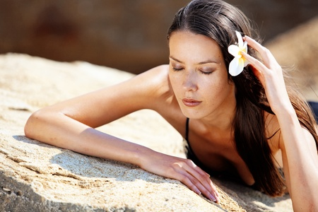 sea flowers: Closeup portrait of beautiful young woman with golden tan resting at beach in summer