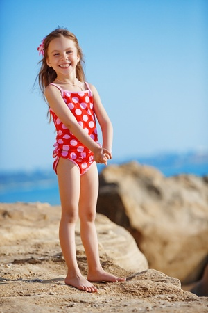 Cute child wearing swimsuit walking at beach in summer photo