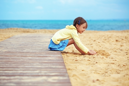 elementary age girl: Child playing at the beach Stock Photo