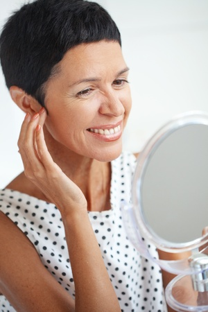 Portrait of beautiful middle aged woman holding cosmetic mirror photo