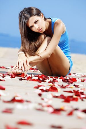 Portrait of young beautiful woman resting at the beach among rose petals photo