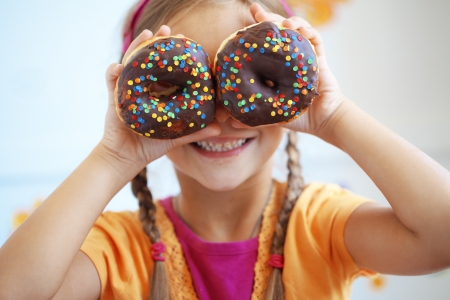 donut: Cute kid girl eating sweet donuts