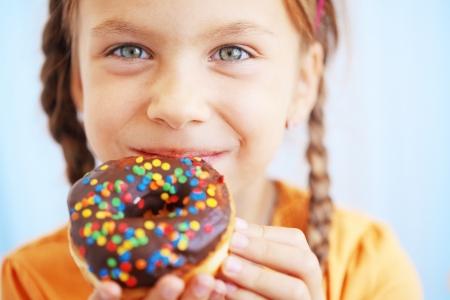かわいい子供の女の子の甘いドーナツを食べる 写真素材
