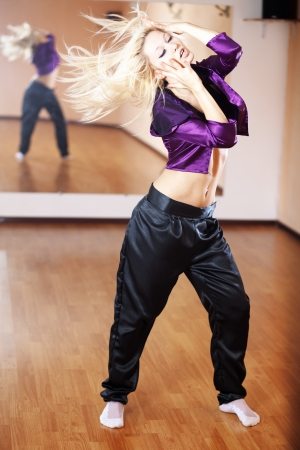 Teenage girl dancing hip-hop in gym classroom photo