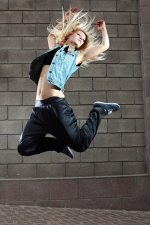 freestyle: Teenage girl dancing hip-hop over the street wall Stock Photo