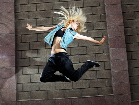 Teenage girl dancing hip-hop over the street wall photo