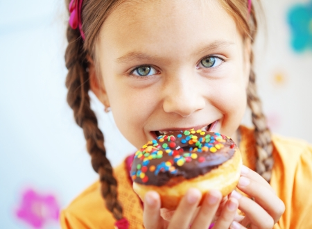 donut shape: Cute kid girl eating sweet donuts