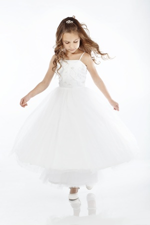 Portrait of a little princess girl wearing wedding dress isolated on white background photo