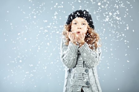 Winter portrait of cute little girl wearing warm cosy clothes studio shot with snow Stock Photo - 16577597
