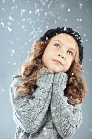 Winter portrait of cute little girl wearing warm cosy clothes studio shot with snow Stock Photo - 16523179