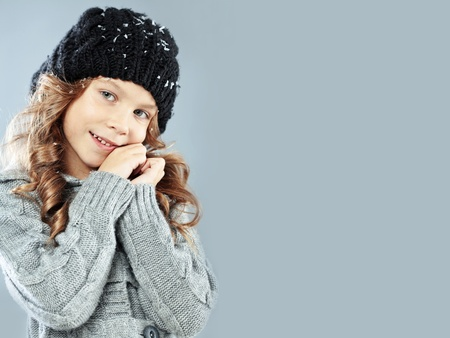 Winter portrait of cute little girl wearing warm cosy clothes studio shot with snow Stock Photo - 16637461