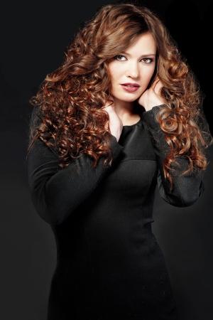긴 곱슬 볼륨 머리를 가진 아름 다운 젊은 여자의 초상화
