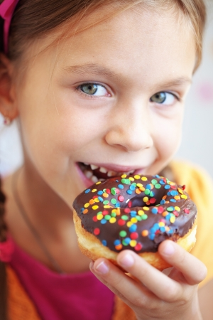 Cute kid girl eating sweet donuts photo