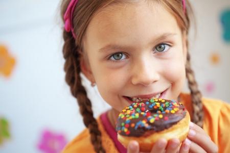 junk: Cute kid girl eating sweet donuts