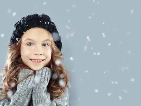 Winter portrait of cute little girl wearing warm cosy clothes studio shot with snow Stock Photo - 16881959