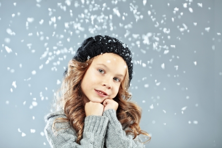 Winter portrait of cute little girl wearing warm cosy clothes studio shot with snow Stock Photo - 16881866
