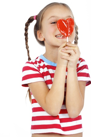 sweet tooth: Child holding heart shaped candy isolated studio shot Stock Photo