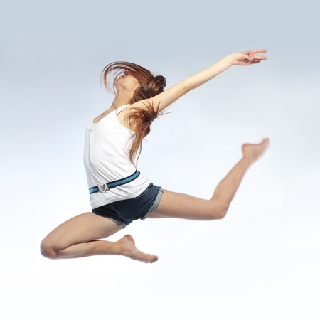 Young beautiful girl doing gymnastick jump studio series photo