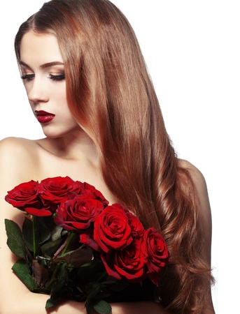 Portrait of a beuatiful young girl holding bouquet of red roses photo
