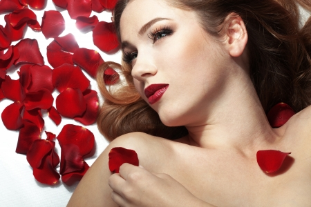 Portrait of a beuatiful young girl laying on sparse rose petals photo