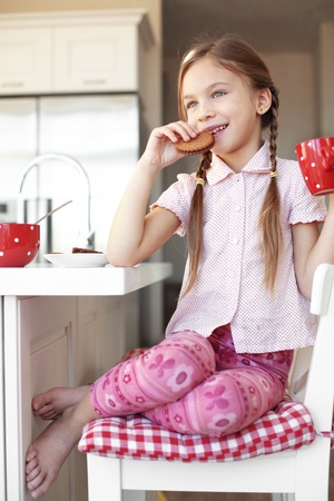 Portrait of a child having breakfast at the kitchen at home photo