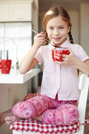 only girls: Portrait of a child having breakfast at the kitchen at home Stock Photo