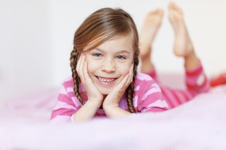 little girl barefoot: Portrait of a little girl resting on the bed in her bedroom
