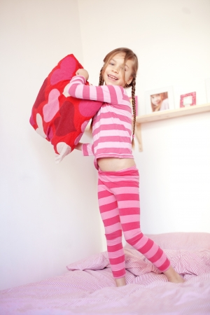 pyjamas: Portrait of a little girl playing with the pillow on the bed in her bedroom