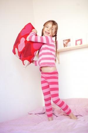 pijama: Retrato de una ni�a jugando con la almohada en la cama en su dormitorio
