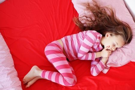 pijama: Retrato de una niña durmiendo poco en la cama en su dormitorio