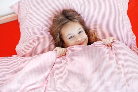 Portrait of a little girl resting on the bed in her bedroom photo