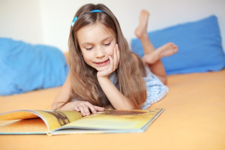 6 years: Portrait of 6 years old child reading book at home