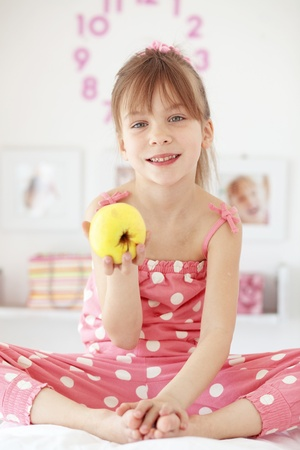 elementary age girl: Casual portrait of cute child eating apple in bed
