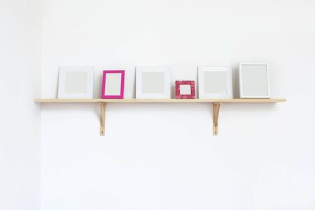 Simple blank photo frames on a shelf over white wall photo