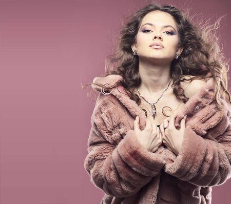 Fashion girl wearing winter fur coat posing over pink photo