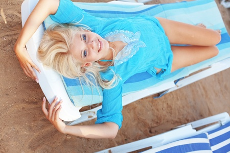 Beautiful blond girl relaxing on beach bad photo