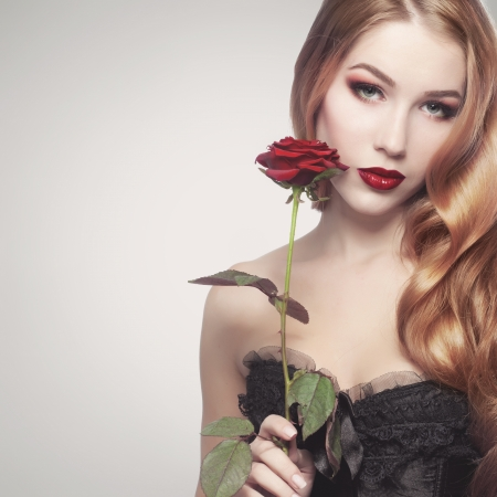 beautiful lips: Portrait of a beuatiful young girl holding a red rose