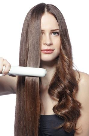 그녀의 빛나는 머리에 스타일러를 사용하는 젊은 아름 다운 여자의 초상화