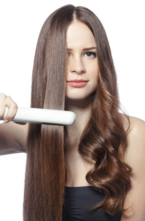long straight hair: Portrait of young beautiful girl using styler on her shining hair