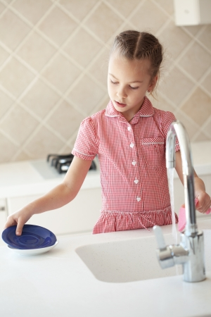 Portrait of a 6 years old girl washing the dishes at home Stock Photo - 18202422