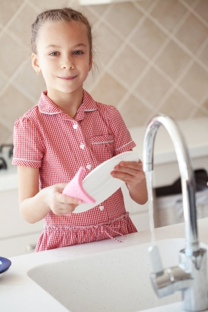 clean dishes: Portrait of a 6 years old girl washing the dishes at home Stock Photo