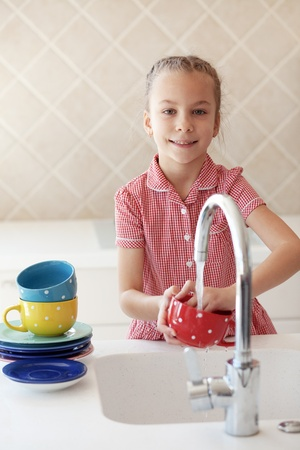 wash basin: Portrait of a 6 years old girl washing the dishes at home Stock Photo