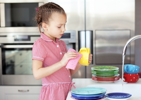 Portrait of a 6 years old girl washing the dishes at home Stock Photo - 18392721