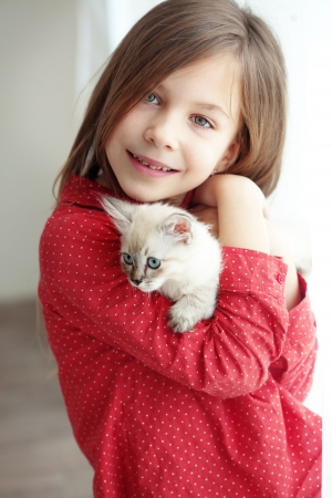 cat playing: Home portrait of adorable child with small kitten Stock Photo